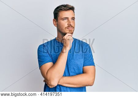 Handsome caucasian man wearing casual clothes thinking concentrated about doubt with finger on chin and looking up wondering