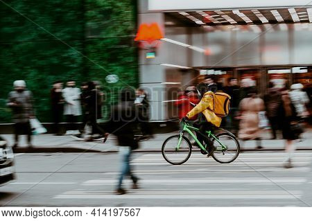 Blurred Image Of A Food Delivery Courier Delivering Food On Bicycle. Cyclist Wearing Orange Coat Car