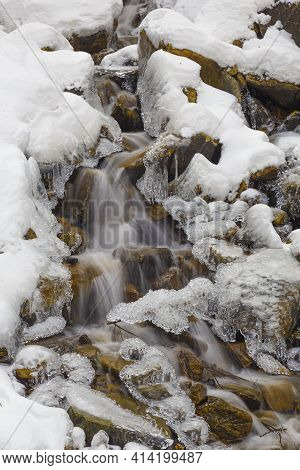 Endless Stream At Winter. Fast Mountain River Covered With Ice And Snow Close-up