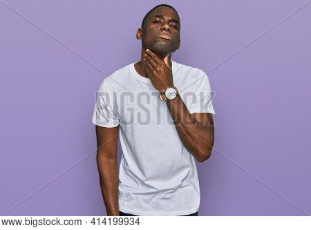Young african american man wearing casual white t shirt touching painful neck, sore throat for flu, clod and infection