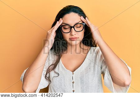 Beautiful middle eastern woman wearing casual clothes and glasses with hand on head, headache because stress. suffering migraine.