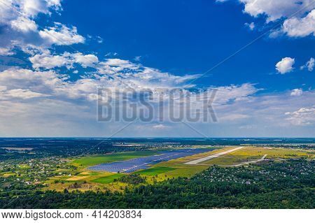 Top View Of The Power Plant With Solar Panels And The Aerodrome. Beautiful Green Fields, Blue Sky, C