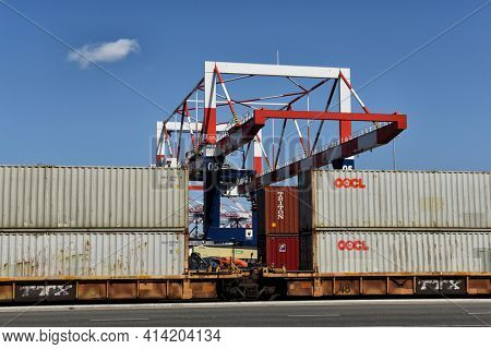 LONG BEACH, CALIFORNIA - 20 MAR 2021: Containers on flat bed train cars with cargo crane, in the Port of Long Beach.