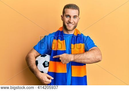 Young caucasian man football hooligan cheering game holding ball smiling happy pointing with hand and finger