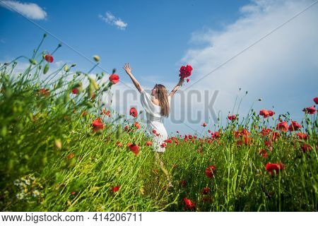 Be Happy. Summer Vacation And Holiday. Pretty Woman In White Dress Walking In Poppy Field. Bride In