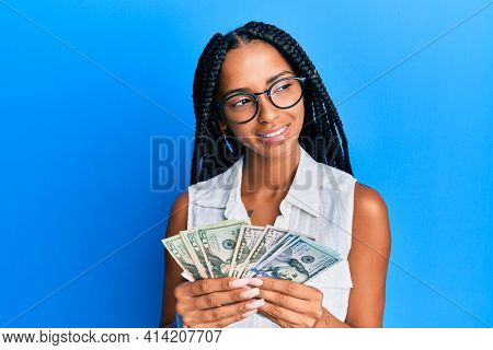 Beautiful hispanic woman holding dollars smiling looking to the side and staring away thinking.