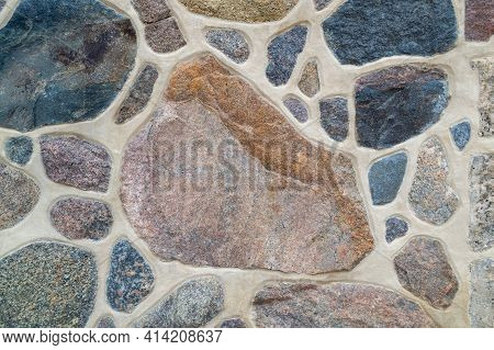 Close-up Of Wall. Stone And Cement. Fragment Of A Colored, Textured Stonewall. Bright Background. Co