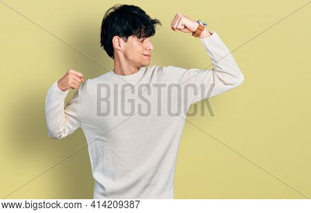 Handsome hipster young man wearing casual winter sweater showing arms muscles smiling proud. fitness concept.