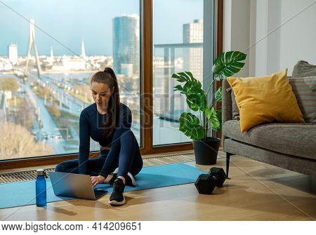 Young brunette in turquoise jumpsuit watches videos on laptop sitting on blue mat near panoramic window and green plant in lodge