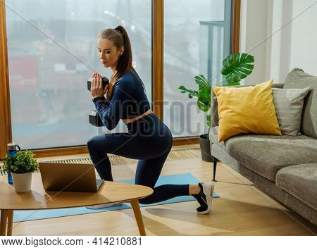 Young brunette does exercises with heavy dumbbell bending knee on blue mat by window with view on city in summer in room