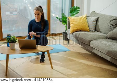 Slim brunette in tracksuit searches videos on laptop standing on coffee table near large window with view on city in lodge