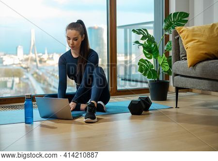 Sportive brunette types on laptop sitting on blue mat near panoramic window with city view and green pot plant on glazed balcony