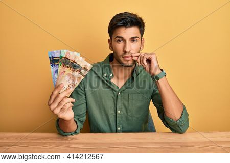 Young handsome man holding canadian dollars mouth and lips shut as zip with fingers. secret and silent, taboo talking
