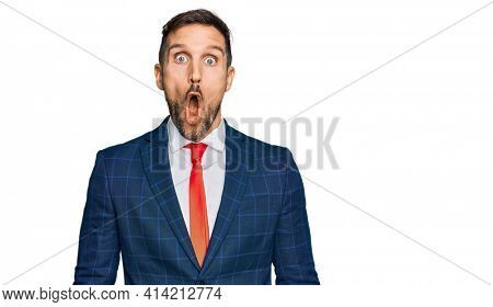 Handsome man with beard wearing business suit and tie afraid and shocked with surprise expression, fear and excited face.