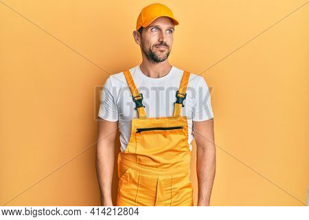 Young handsome man wearing handyman uniform over yellow background smiling looking to the side and staring away thinking.