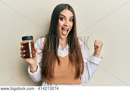 Beautiful brunette young woman holding soluble coffee pointing thumb up to the side smiling happy with open mouth