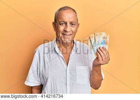 Handsome mature man holding swiss franc banknotes looking positive and happy standing and smiling with a confident smile showing teeth