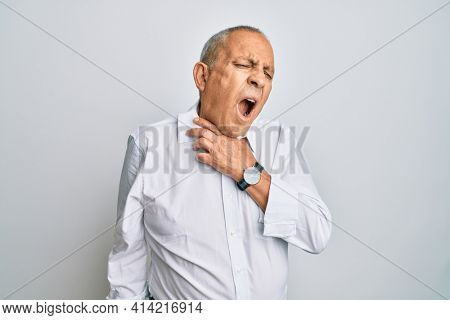 Handsome senior man wearing casual white shirt touching painful neck, sore throat for flu, clod and infection