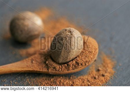 Nutmeg .whole And Ground Nutmeg In A Wooden Spoon Close-up On A Schiffer Background.