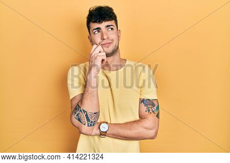 Young hispanic man wearing casual t shirt thinking concentrated about doubt with finger on chin and looking up wondering
