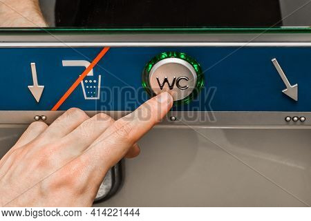 A Man's Hand Presses A Finger On The Flush Button In A Modern Toilet Of The Stadler Electric Train,