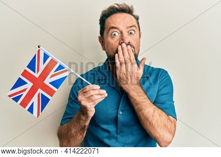 Middle age man holding united kingdom flag covering mouth with hand, shocked and afraid for mistake. surprised expression