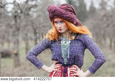 Extravagant Redhead Young Woman Wearing Ethnic Jewelery, Clothes And Turban With Unusual Makeup Danc