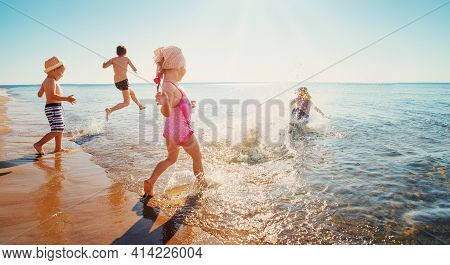 Boys And Girls Playing On The Beach On Summer Holidays. Children In Nature With Beautiful Sea, Sand