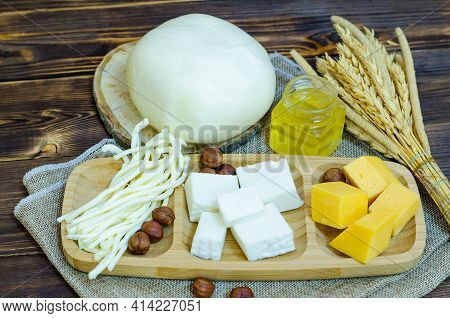 Set Of Different Cheese On A Wooden Plate. Cheese Platter With Nuts And Honey On A Wooden Background