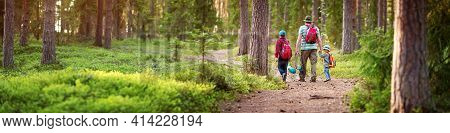 Father And Boys Going Camping With Tent In Nature. Man With Sons With Backpacks Walking In The Fores