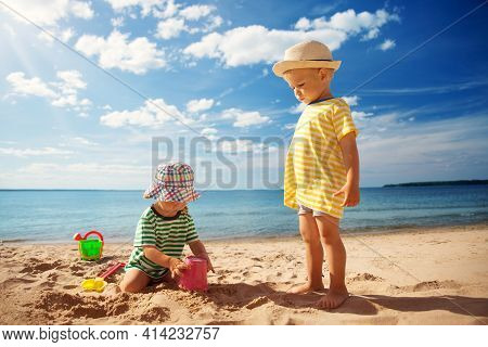 Boy And Girl Playing On The Beach On Summer Holidays. Children In Nature With Beautiful Sea, Sand An