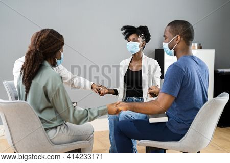 African Worship Group Holding Hands In Face Masks