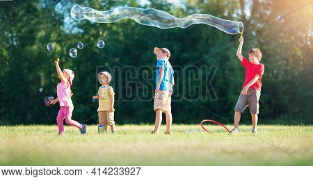 Happy Children Having Fun In Grass On Sunny Summer Evening. Kids Outdoors In Nature Blowing Bubbles
