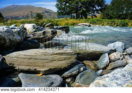 Close Up White Surging River Water And Large Rocky Edge In New Zealand.