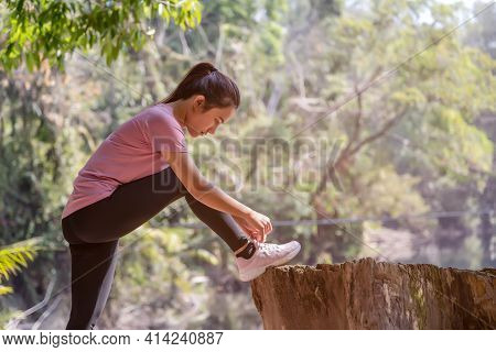 Asian Woman Tying Shoe Laces. Female Sport Fitness Runner Getting Ready For Jogging Outdoors. Concep