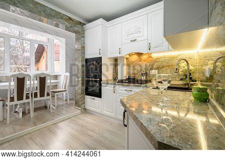 Modern classic luxury white kitchen interior with dining zone, cozy design