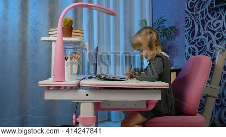 Child Schoolgirl Learns Lessons With Teacher Being At Home Sitting At Table Using Digital Laptop Com