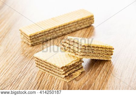 Whole Wafer And Halves Of Broken Wafer With Chocolate Filling On Brown Wooden Table