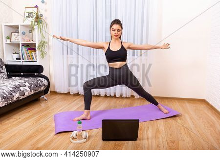 Yoga Online On The Laptop. Healthy Lifestyle. Girl Doing Yoga At Home. Fit Woman Doing Yoga And Watc