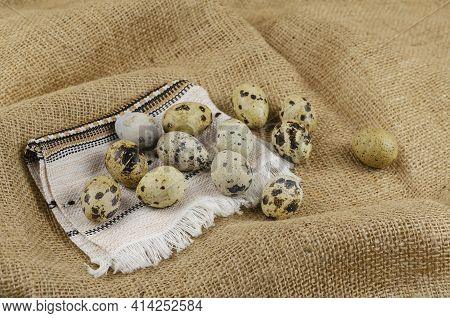 Quail Eggs And Ethnic Napkin On Sacking. Raw Eggs And A White Fringed Napkin. Close-up, Selective Fo