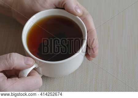 Close-up Of Male Hands And A Mug With Tea On A Beige Surface. White Ceramic Mug Full Of Black Tea. T