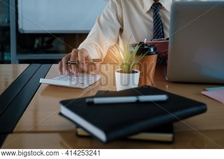 Young Accountant Man Analyzes Financial Data Using Calculator And Laptop Computer To Compute And Sum
