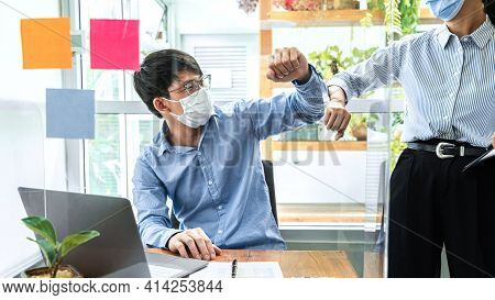 Two Business Colleagues Avoid Handshake Greeting Each Other By Bumping Elbows When Meeting In Office