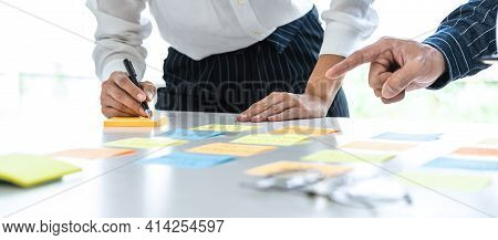 Two Creative Business People Meeting And Planning Use Post It Notes Sticky Note On Desk To Share Ide