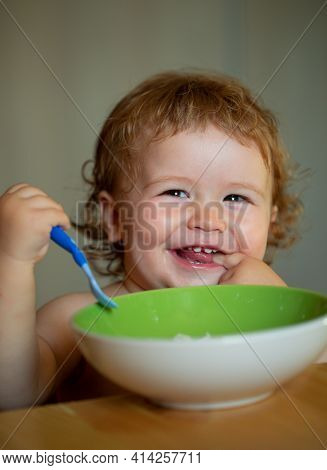 Smiling Baby Eating Food. Funny Baby Eating Food Himself With A Spoon On Kitchen. Healthy Nutrition