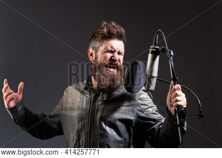 Singer Singing Rock. Expressive Singer With Microphone. Sound Producer Recording Song In A Music Stu