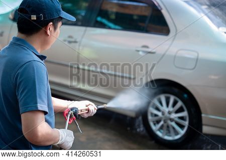 Close Up Of A Man In Uniform Washes His Car With A Large Head Of Water From A Karcher And Washing Ca