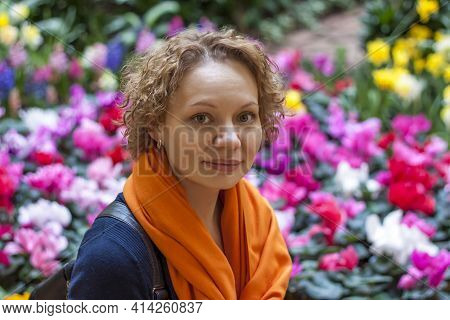 Portrait Of A Curly-haired Girl On The Background Of A Flower Bed. Close-up Of The Face Of A Young B