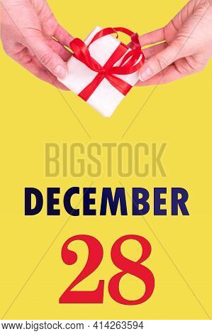 December 28th. Festive Vertical Calendar With Hands Holding White Gift Box With Red Ribbon And Calen