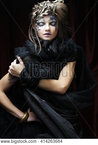 Halloween and party concept. Beautiful Gothic Princess. Young woman wearing black dress, with creative make up and hair style over dark red background.